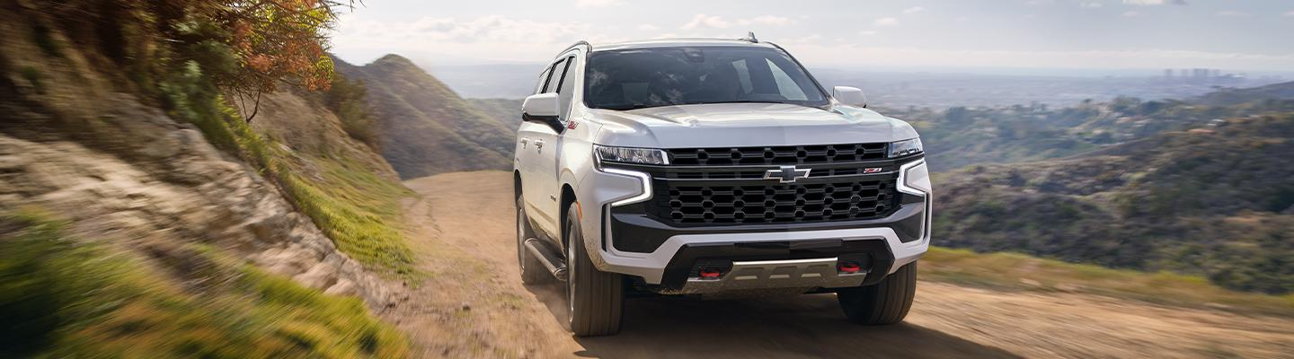 White 2021 Chevy Tahoe in motion through an offroad trail.