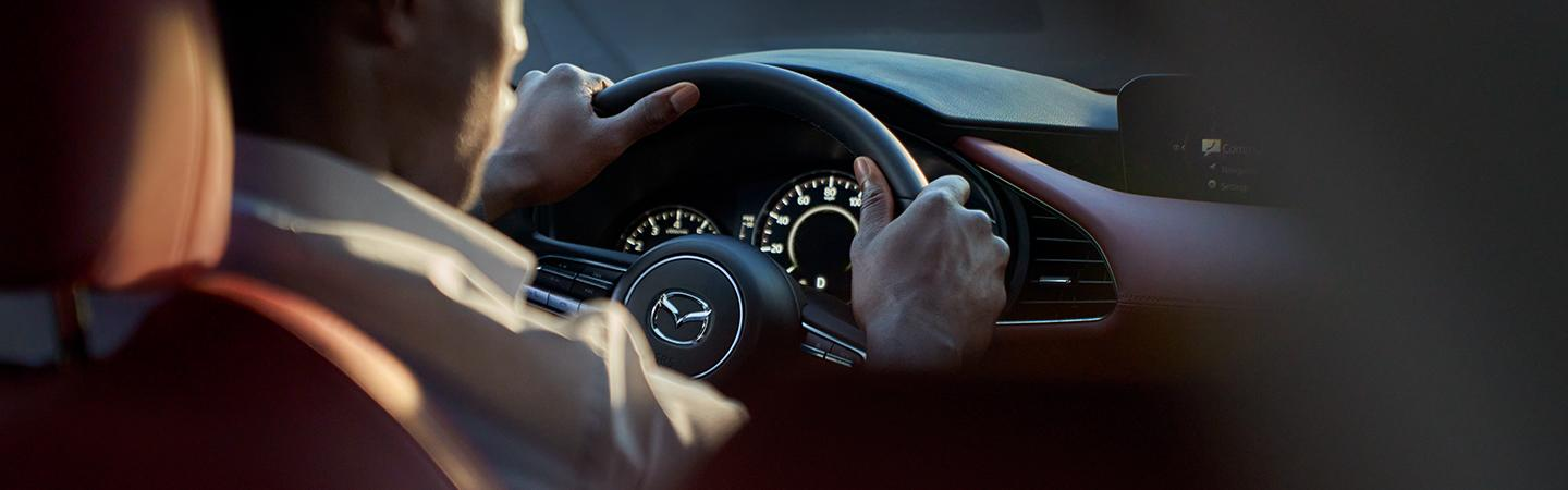 Close up view of a man driving a Mazda3