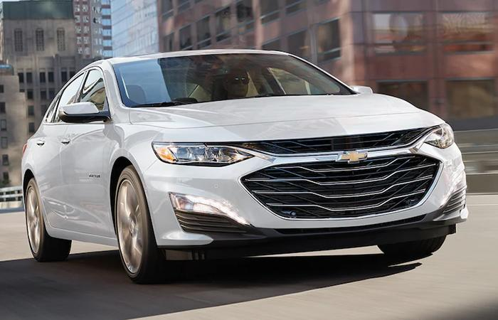 Angled profile of a white Chevy Malibu in motion