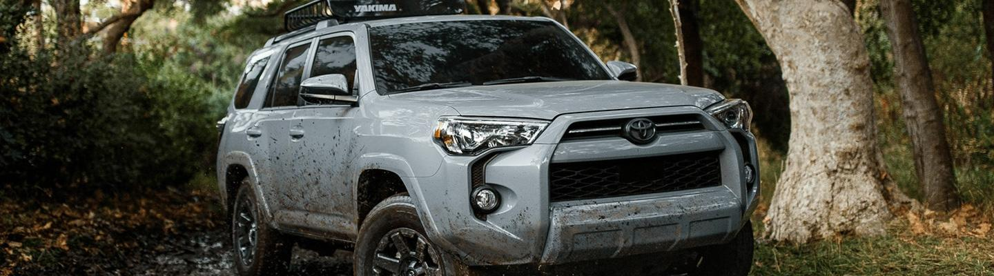 Angled side profile of a white Toyota 4Runner driving through mud