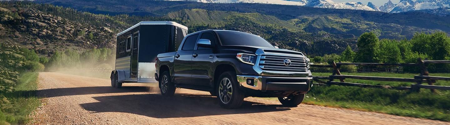Angled front profile of a black Toyota Tundra towing a trailer