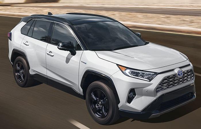 Angled profile of a white Toyota RAV4 Hybrid in motion