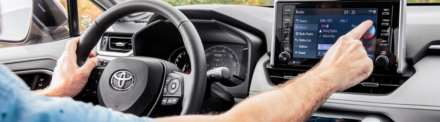 Close up view of a driver using their infotainment system in a Toyota RAV4