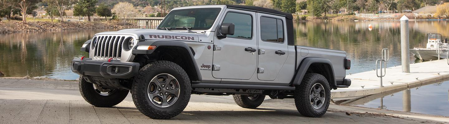 Side view of a white 2021 Jeep Gladiator driving up hill
