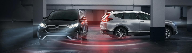 2 Honda CR-V vehicles parked in a garage together