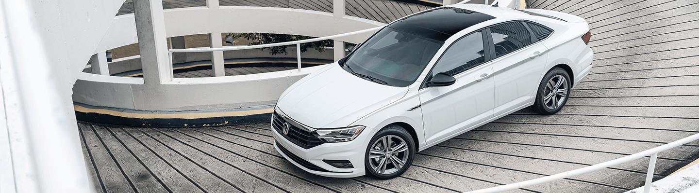 White 2021 VW Jetta in motion down a parking garage