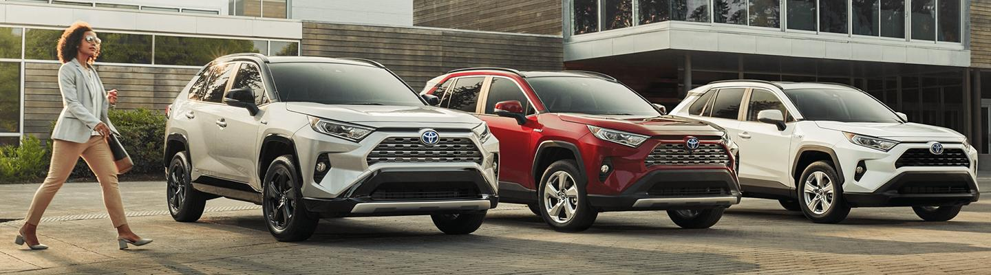 Three 2021 Toyota RAV4 lined up parked with Woman walking next to them