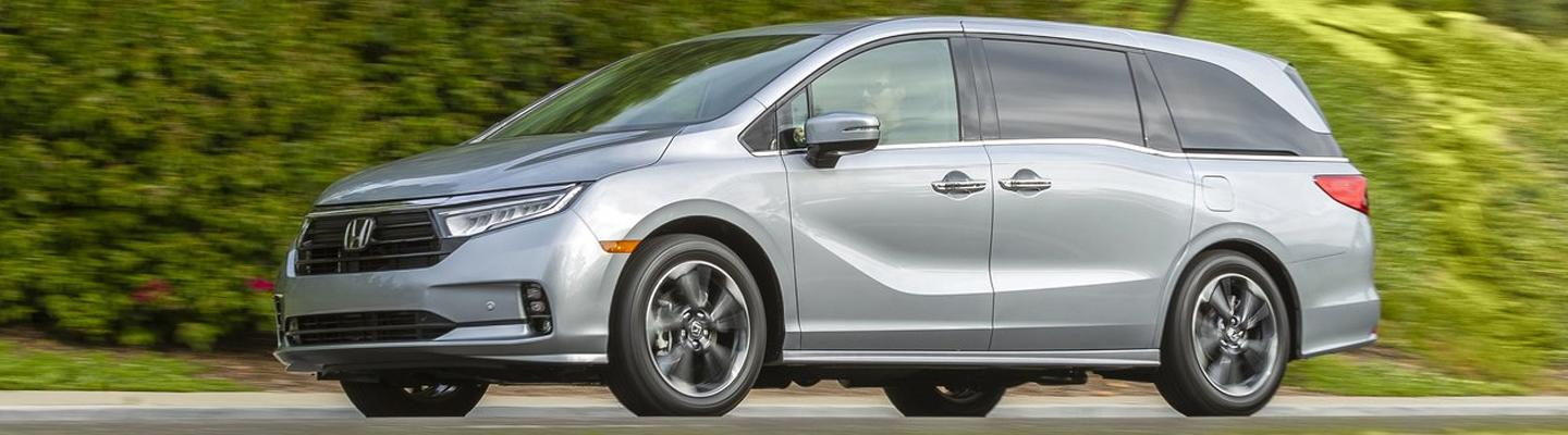 Side profile of a silver Honda Odyssey in motion