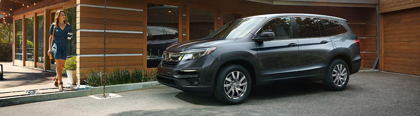 A driver walking to their Honda Pilot outside of a coffee shop
