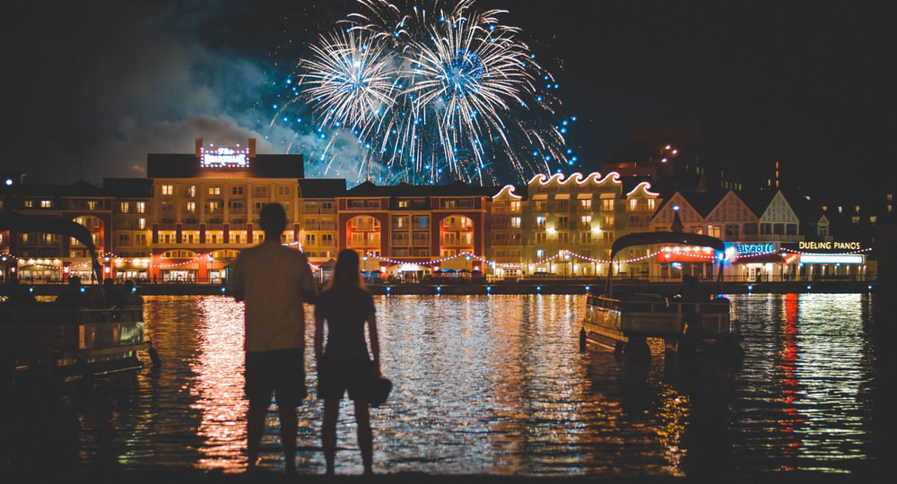 two people standing beside body of water watching fireworks while considering moving to orlando