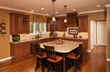 Inset stained Alder cabinetry and decorative hood.