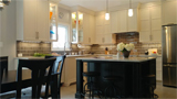 Traditional kitchen design with glass cabinets,matching wood hood and island seating.