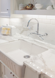 Real marble countertops, white porcelain farmhouse sink, and polished nickel faucet.