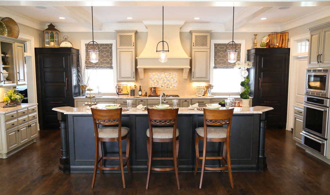 Kitchen with a variety of cabinets from light to dark and an island with bar stools