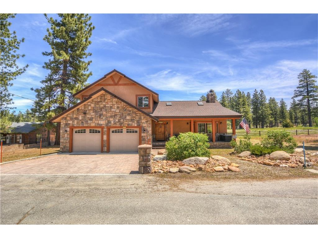Gorgeous, custom home on West End of Big Bear near Metcalf Bay with lake views and walking easement down to Big Bear Lake! You'll love the open, feeling when you step into this immaculate, custom home! Vaulted ceilings with skylights, wood flooring and a floor to ceiling rock fireplace in the massive living room welcome you in. Kitchen has granite counter tops and stainless steel appliances with breakfast bar for entertaining family and friends! Comes with separate laundry room and separate walk in pantry. 4 bedrooms, 3.5 bathrooms make this an ideal mountain getaway for the crew. The Master Bedroom has its own deck with beautiful views of acreage and the lake! Bathrooms have custom granite and travertine accents. Great setting for those summer BBQ's on the back deck with spa which overlooks the back acreage. Enjoy the covered front porch for Summer rain storms or Winter storms as they set in! Must see this gorgeous home with all of its amenities to appreciate!