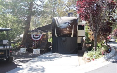Beautifully landscaped corner lot with a designer log wall that promotes privacy from the street. This lot has been upgraded with pavers has mature trees that offer all day shade, privacy, and serenity. Coach is available outside of escrow. Located within the spectacular lake front community of Big Bear Shores. Big Bear Shores is a gated RV community that offers all the refinements of a country club in a forest setting, beautifully landscaped grounds with mature towering trees a spectacular and waterfall entry. A three story club house with fireplace, commercial kitchen, 2 bars, big screen TV's, entertainment areas and pool tables. Other amenities include a gym/workout room, sports court (tennis, basketball & pickle ball), private storage locker, laundry facility, swimming pool,
