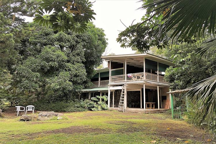 It is hard to imagine ever being bored in this home. First of all there's its atypical size. There's 3192 sf of living area including 3 bathrooms and 3 baths and a 2500sf of covered lanai on 2 acres. All that space work well to make this property unique and interesting.  And then there's the design that takes advantage of tropical living The house is multi-level with an expansive covered lanai in nearly all sides of the house. At the ground level there's a 2-car garage and a workshop. After passing a koi pond and entering the double front door, one goes through a foyer. A short flight of stairs leads to the living area proper. Immediately, one notices sunlight streaming through the many energy-efficient custom windows.   There is plenty of room for entertaining and the tools and appliances for it. The kitchen's Wolf stove, Sub-zero refrigerator, Sapele cabinets and granite countertop will make a woman's heart flutter with appreciation and possibly transform a cook into a gourmet chef. The deck-patio has a jet tub that makes you feel like your bathing in the middle of a forest.  Including TMK 3-1-5-47-26