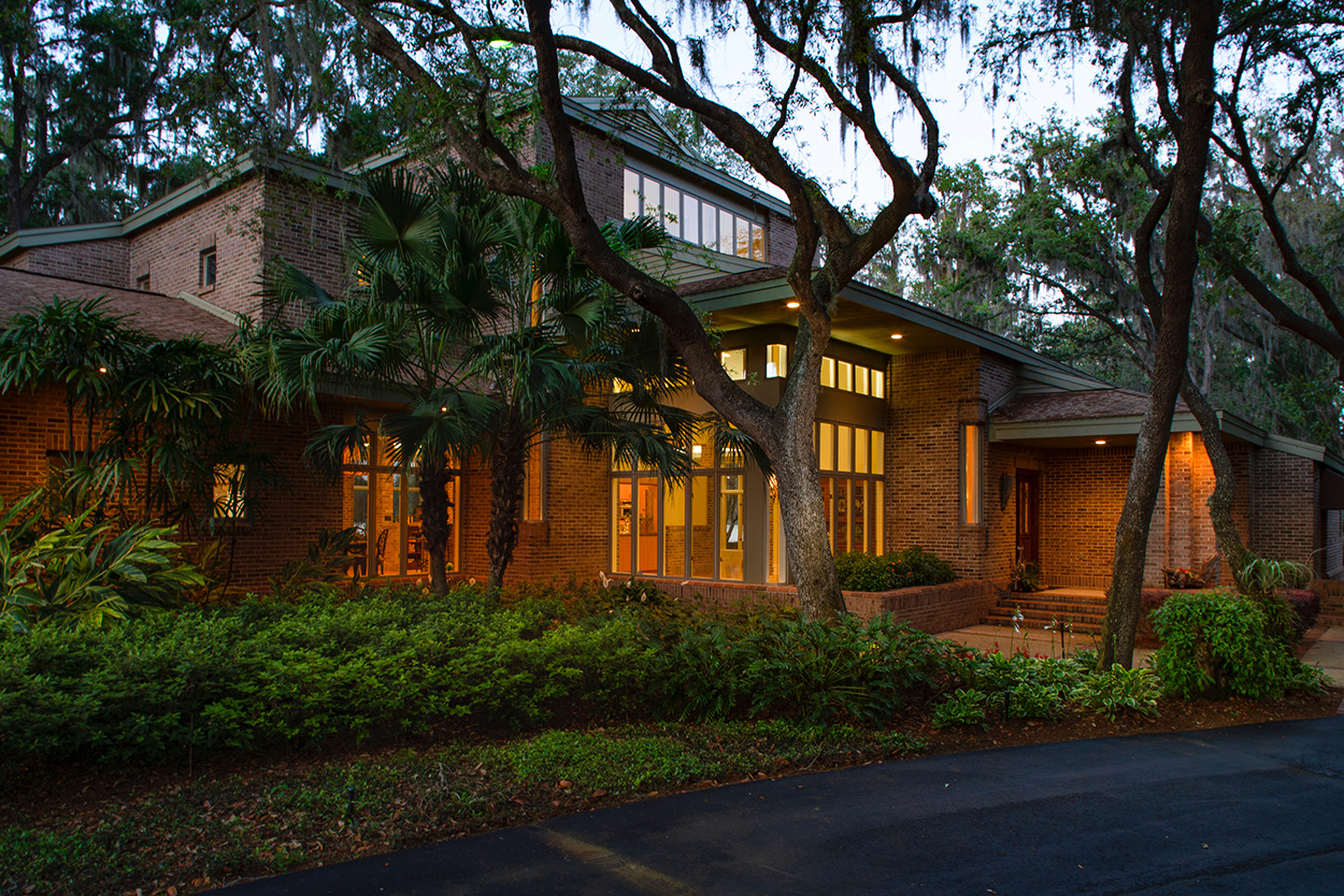 Originally owned and built by the Starkey family. This custom home is situated perfectly on over four acres of pristine Florida flora and lakefront living. Drawing design inspiration from legendary architect Frank Lloyd Wright and his renowned prairie homes of the early 1900s. It includes many of the popular elements he was known for; attracting the outdoors inside, corner glass windows, open floor plan, customary brick interior and natural materials throughout make this not just a home, but an experience. Extensively renovated in 2015, the kitchen includes distinctive red fusion granite, leaded-glass pass-through doors, and copper range vent accenting the interior brickwork. Outdoor kitchen and private dock provide unrivaled access to 530 feet of lake frontage on Lake Anne.