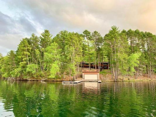 Impressive Kawaga Lake property nestled within the towering red & white pines w/ 2.27 acres and 308' sandy swimming frtg. Featuring 4BR, 5BA & just over 4,000 sq ft this home checks many boxes. You'll be left speechless upon entering into the massive luxurious yurt-style great room. Here is one of the most impressive entertaining rooms featuring cathedral knotty pine ceilings, endless panoramic lake views, wetbar, FP, & updated kitchen with granite & high-end appliances. There is a 3 season porch, massive wrap-around deck, & walk-out basement. Outside you will find the boathouse with a party deck, permanent piers, bonfire pit, & 3 car insulated garage. This is a premier location with views of University of WI owned forest, Camp Kawaga's slalom water ski course, & Beer Can Island. Enjoy the best of both worlds being located in a quiet bay yet being on the Minocqua Chain! Boat to all the restaurants/bars, watch the water ski shows via boat, the options are endless