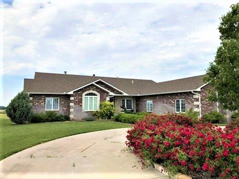 Exclusively listed - Enjoy country living in this beautiful home sitting on 5 acres. Entire home built with 18 inch eco-block walls w/ brick surrounding it. Home has 4 bedrooms & 4 1/2 bathrooms. Upstairs master bath is equipped with jacuzzi tub, large walk-in closet with laundry hook ups. Walk out of the master onto your balcony which spans the entire width of the house. Surround sound throughout main level & outside deck area. Kitchen has beautiful custom cabinetry, 2 convection ovens with warming drawer and a large walk in pantry. Family room has custom roman shades with gas burning fireplace. Relish in your walkout basement with 9 foot ceilings, all new carpet throughout, large wet bar and wood burning fireplace. There is also laundry hookups in the basement. The triple car heated garage boasts a heated driveway and garage floor. Enjoy your evenings watching the sunset on the deck, looking at the beautifully landscaped rocks brought in from Colorado.
