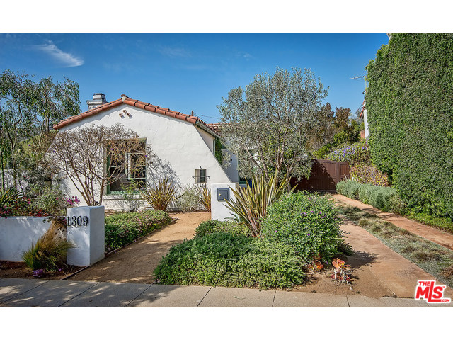 Absolutely charming Spanish style home in Sunset Park area of Santa Monica. Walk through front door to spacious, light-filled living room with modified barrel ceilings. The wood-burning w/gas starter fireplace is the focal point of the room, with beautiful wood mantle and stone façade. Original hardwood flooring throughout. Dining room has extra-large windows, offering great light and coved ceilings. The updated kitchen has beautiful granite countertops & frosted glass cabinetry and island with breakfast-bar counter. Two secondary bedrooms share a full bath. Master bedroom offers a 3/4 bath, two walk in closets and doors opening to a lovely patio facing the backyard. Gorgeous landscaping & hardscaping around the home was completed in 2011. Storage in the detached 2-car garage was installed in 2013. An absolutely lovely home inside & out, a must to check out!
