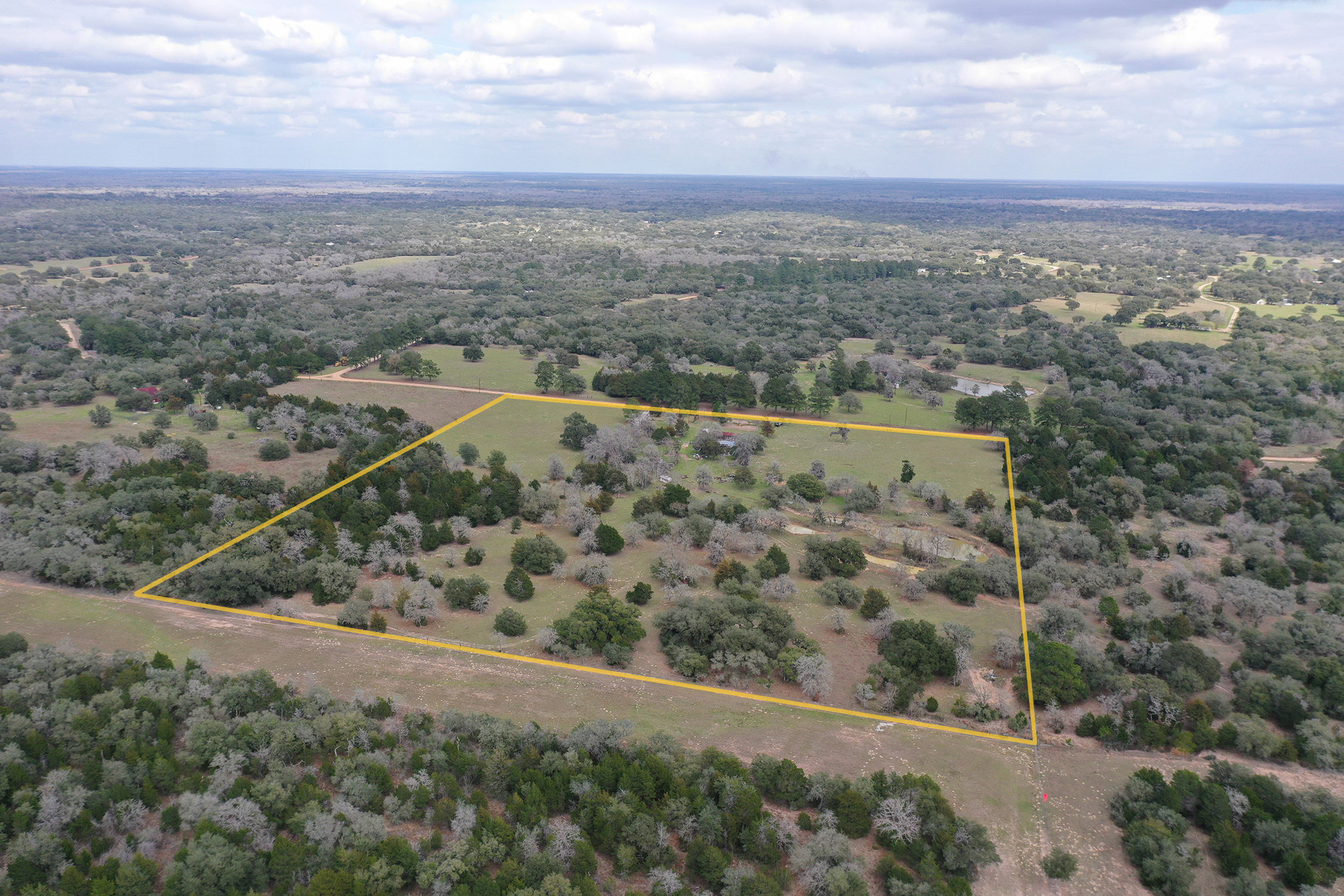 With some pipe fencing, a water well, septic and electricity already in place, this 17.42 acres of land is ready for a new owner. Look for the bluebonnets, pear, plum, peach, Japanese plum and crepe myrtle trees to bloom in the spring. The owner has cleared the original thick trees, so now it's well suited for cattle or horses, with tank ponds, fencing in good condition, and cattle pens and chute. Turkeys, deer, hogs and coyotes are some of the wildlife you'll most likely see at some point. Located toward the end of the end a dead-end road, there's very little traffic driving by, so all you can hear is mother nature. An existing manufactured home can use some TLC, or you can use the existing utility set up for a new home or RV.