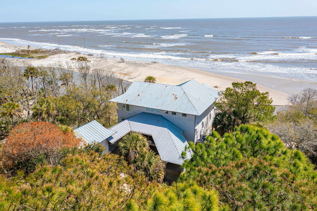 Panoramic beach and oceanfront views tailored to private island living is unmatched in the Charleston and surrounding areas.  Don't miss this opportunity to own a truly unique beachfront retreat for all of your friends and family to enjoy for many, many years to come.  Ocean views from each room throughout the house taking advantage of breathtaking unobstructed sunrises, ocean breezes and views for miles and miles.  From the minute you rise up the expansive staircase into the stain glassed entrance into this amazing property you'll enjoy the peace and tranquility of hearing the waves crash into the surf from your open family room and kitchen leading into your private porch just steps from the water. The open floor plan incorporates a well-designed Chef's kitchen, butler's pantry and oversized windows surrounding the eat in breakfast nook with a large double-sided living space defining the dining and living areas.  Stunning wide planked pine floors, accented metal works, modern finishes, stunning views and an abundance of natural light fill this one of a kind property.  With elevator entry to all three levels one can easily access the master suite and guest bedrooms each with their own ensuite bathroom.  The sizeable master suite with sprawling ocean views provide the ultimate getaway for one to relax and take in the one of a kind beachfront views.  The retreat is situated off of the main level and provides a unique location for one to have an additional office, art studio or just getaway from it all with a full suite bathroom and two Murphy beds.  This is the absolute definition of privacy, luxury and pristine private island living!