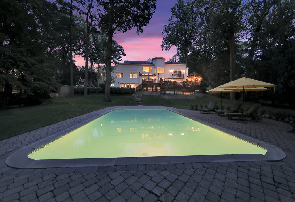 Picture yourself in this home set on a private 1-acre property on Tenafly's prestigious east hill area with top rated schools, a 20x40 heated pool, the amazing outdoor living offers a Brazilian IPE Wood 2 tier deck w/built in kitchen, heavy duty BBQ, refrigerator, a Gazebo w/fire pit... The Soaring ceilings & ceiling high windows create a dramatic first impression the moment you enter. A custom-built loggia consists of 4 bdr of which 1 en-suite bedroom 3 additional large bdr, 1 fbth. Separate a stunning large master suite with a fireplace, a seating area a spa grade master bath and a balcony overlooking the private Shangri-La.  This house has been expanded, rebuilt and renovated in the early 2000's & 2010's walk out family room adjacent to en-suite maids bedroom, finished basement, 2 FPL Wood & electric, a gourmet kitchen, Surround System, top appliances, a wine closet, an electric car charger and more, taxes less than $50k