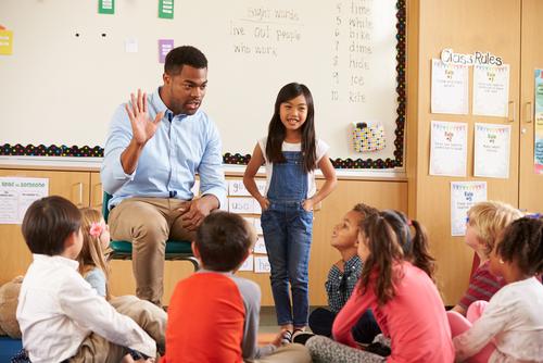 children listening to one another speak in the hallway at school