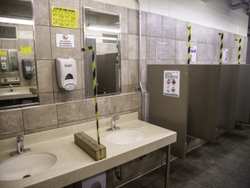 Solid Lexan barriers separate the sinks and urinals in the men's restrooms.