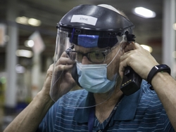 A Maintenance Business Leader wears his required mask and face shield.