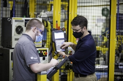 """Two employees on GE Appliances' Industry 4.0 Development Program – Jordan Klotz (left) and Collie Crawford (right) – discuss short cuts for """"pick and place"""" routines on the robot teach pendant for the new automated dishwasher spray arm assembly cell."""