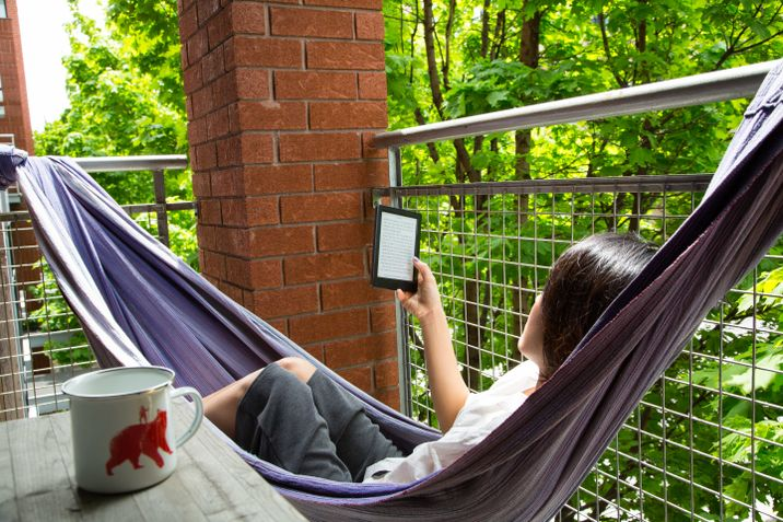 Yunjung Na reading from her Kobo eReader in a hammock on the balcony
