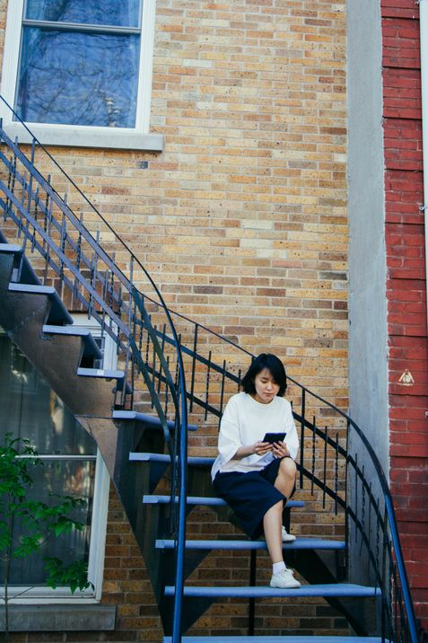 Yunjung Na reads her Kobo on the balcony before returning to Toronto from Montreal