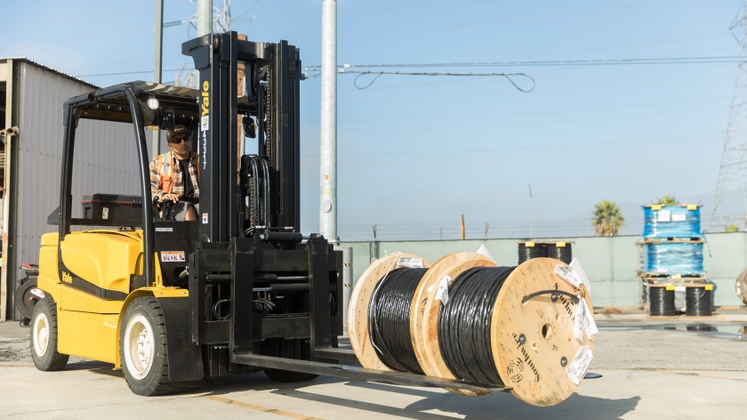 SCE's electric forklifts can do the same work as diesel and propane models like moving large spools of wire.