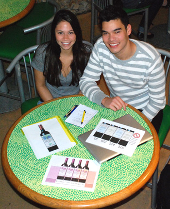 Seniors Kalina Ward and Daniel Mabasa display some of the mock wine labels their team has created for their capstone project. They credit the capstone with helping them learn more about their working styles, and turning the team into friends instead of just classmates.