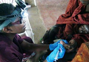 Click to open the large image: UCLA nurse Millicent Manyore treating Kenyan baby