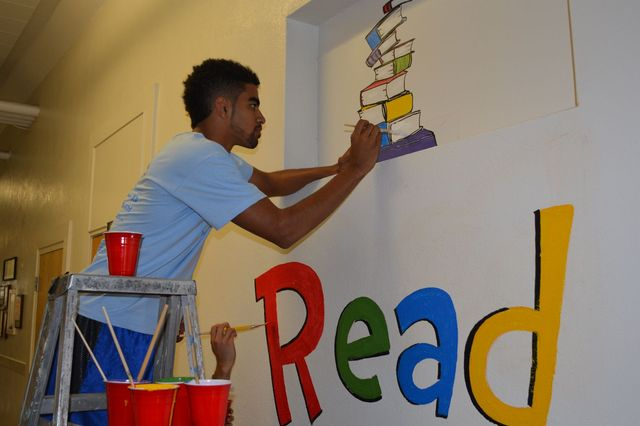Student painting book mural