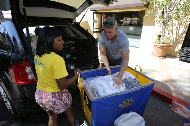 A student volunteer helps a parents unload