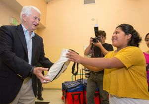 Click to open the large image: Volunteer Day 2014 Chancellor hands out a bag.
