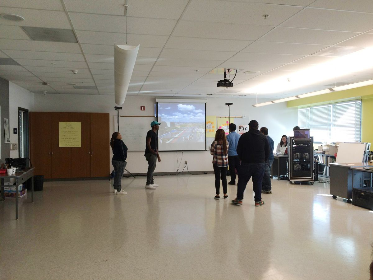 High school students look at a 3-D cyber mural they created