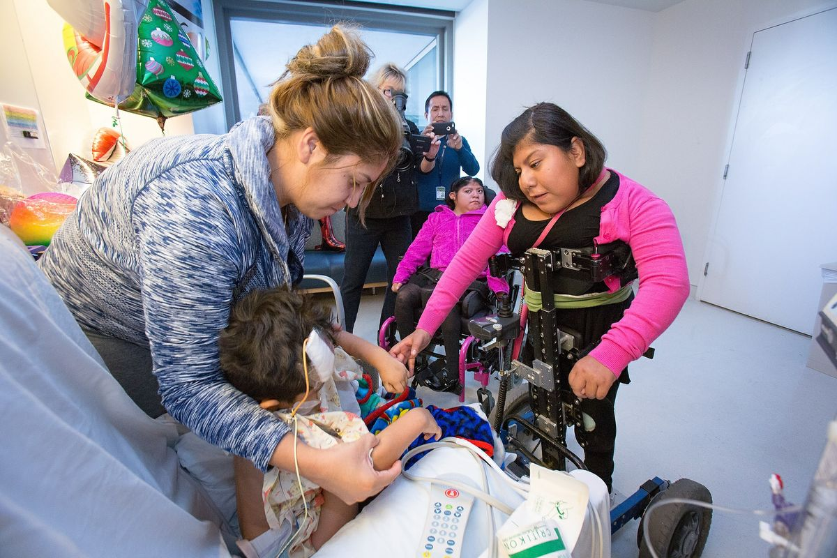 Josie Alvarez with a Mattel Children's Hospital patient. Her twin sister, Teresita, in a wheelchair, looks on.