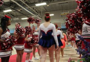 Cheerleaders and athletes competing in rhythmic gymnastics