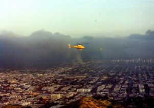 Helicopter flies over burning parts of the city