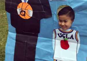 A preschooler poses with a drawing of Coach John Wooden