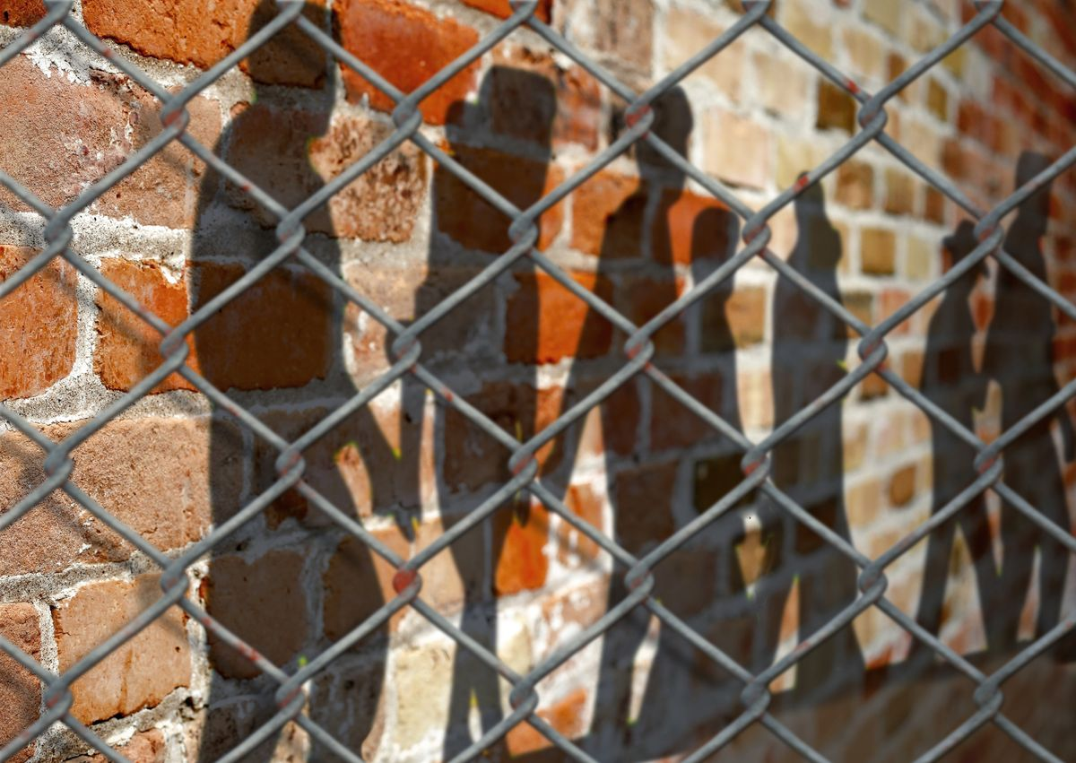 Image of youths behind chain-link fence