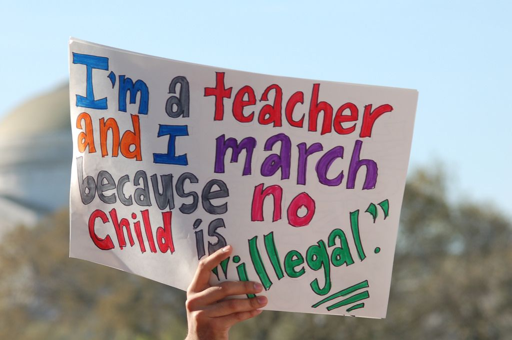 Teacher with immigration sign