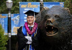 Graduate at bear statue
