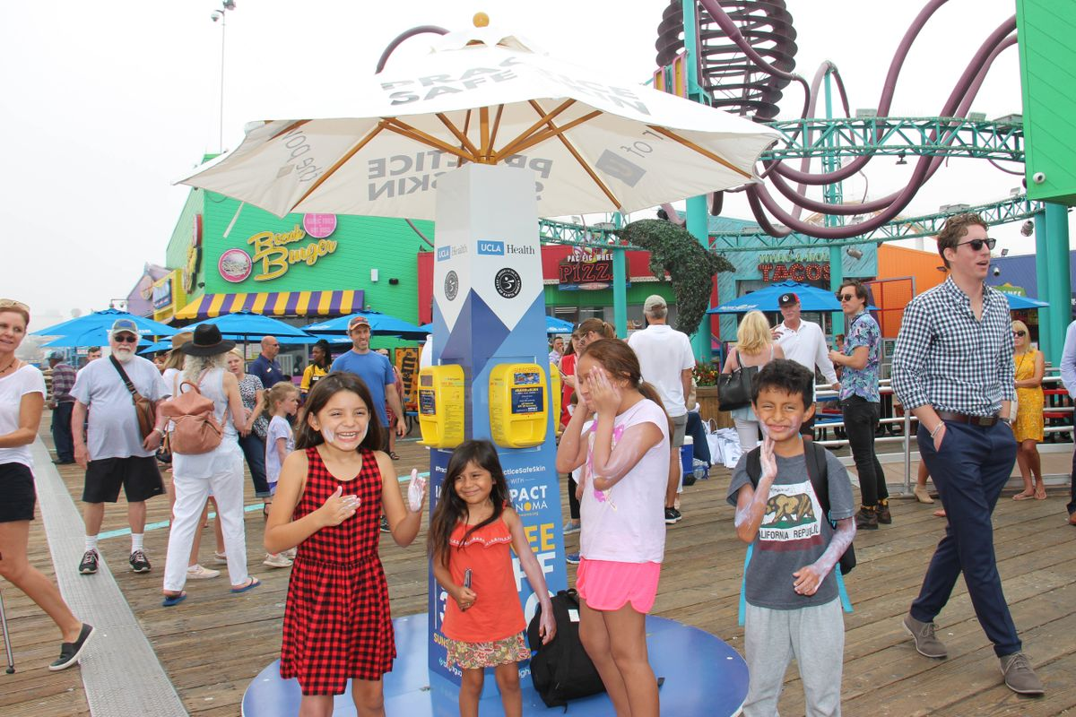 Kids use sun safety kiosk