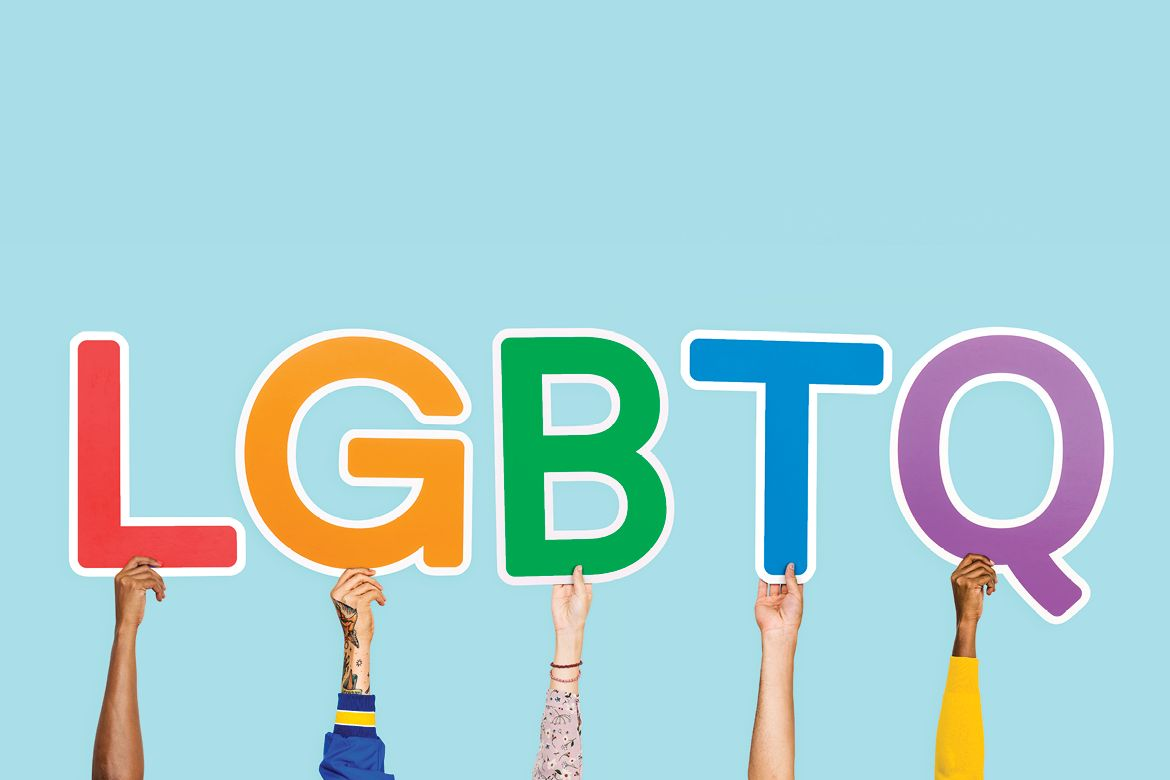 Hands holding up letters LGBTQ
